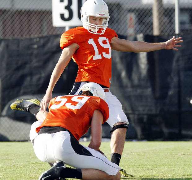 photo - OKLAHOMA STATE UNIVERSITY / OSU / COLLEGE FOOTBALL: Oklahoma State kicker Ben Grogan kicks after the ball is held by placeholder Michael Reichenstein in a drill during the first full pad practice of the fall on August 6, 2013. Photo by KT King/ for The Oklahoman
