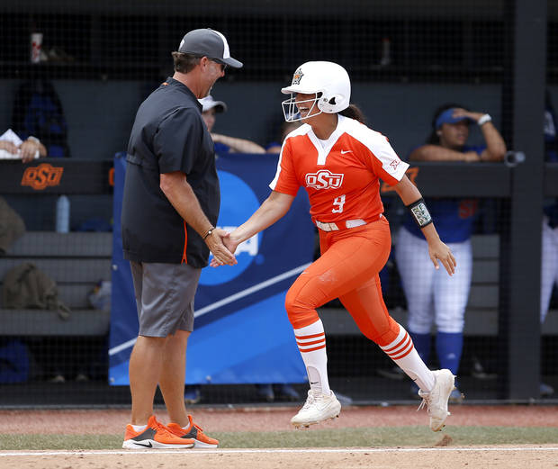 OSU's Chyenne Factor (9) celebrates a grand slam with head coach Kenny Gajewski in the sixth inning during a NCAA regional softball game between the Oklahoma State and Tulsa in Stillwater Friday. [SARAH PHIPPS/THE OKLAHOMAN]