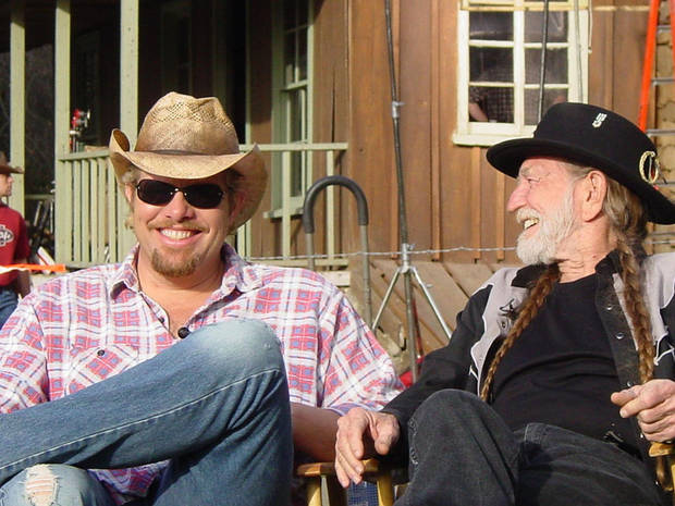 "** ADVANCE FOR FRIDAY, OCT. 10 ** Toby Keith, left, and Willie Nelson share a laugh during the video shoot for their duet ""Beer for My Horses,"" in this summer 2003 publicity photo. Veteran country singers like Nelson are finding the only way to radio airplay these days is to be hitched to younger stars.  (AP Photo/HO)"