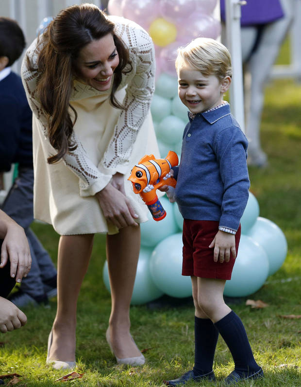 Britain's Catherine, Duchess of Cambridge, looks on as Prince George plays with a bubble gun at a children's party at Government House in Victoria, Thursday, Sept. 29, 2016. (Chris Wattie /The Canadian Press via AP, Pool)