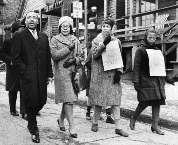 photo -  Dr.  Martin  Luther  King,  Jr., left, and his wife, Coretta Scott  King, second from left, join pickets during a tour of an Atlanta slum area, in this Feb. 1, 1966 file photo. (AP Photo)
