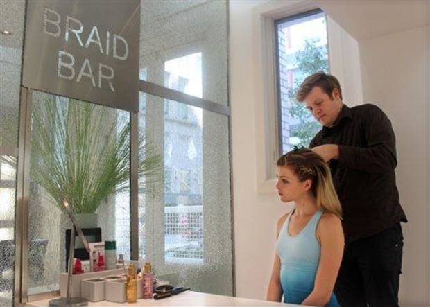 photo - In this Aug. 1, 2012 photo, stylist Cliff Freeman braids the hair of Danielle Maddox, 25, at Maxine salon's Braid Bar in Chicago. Salons from Los Angeles to New York and cities in between are opening