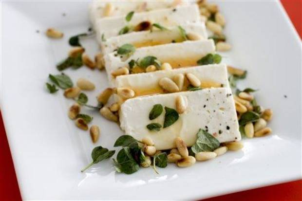 photo - In this undated image, feta cheese and honey are shown served on a platter in Concord, N.H. (AP Photo/Matthew Mead)