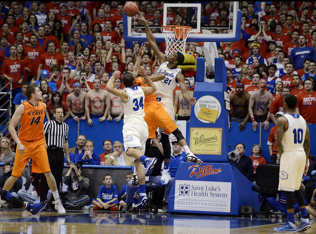 photo - Kansas' Joel Embiid, top middle, rejects a shot by Oklahoma State's Markel Brown during the first half at Allen Fieldhouse in Lawrence, Kan., on Saturday, Jan. 18, 2014. (Rich Sugg/Kansas City Star/MCT)