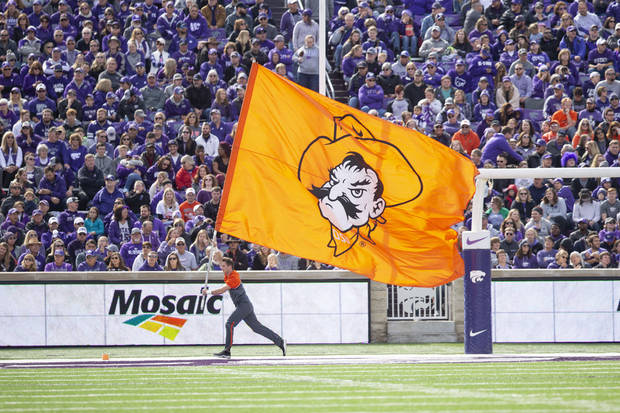 A member of the OSU Spirit Squad runs with the Pistol Pete flag during Saturday's game. [PHOTO BY BRUCE WATERFIELD, Courtesy OSU Athletics]