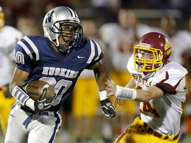 photo - Edmond North&#039;s Richard Morrison runs past Putnam City North&#039;s Creighton Decker during a high school football game at Wantland Stadium in Edmond, Okla., Friday, September 21, 2012. Photo by Bryan Terry, The Oklahoman