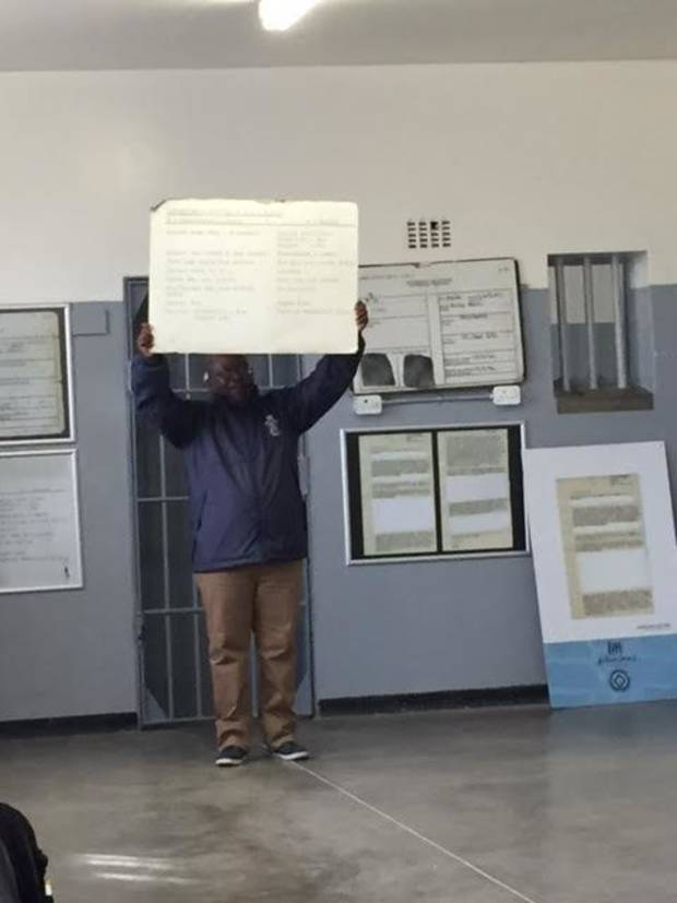 A political prisoner who spent nearly seven years on Robben Island holds up a placard detailing what inmates got for food. Hint: It ain't much.
