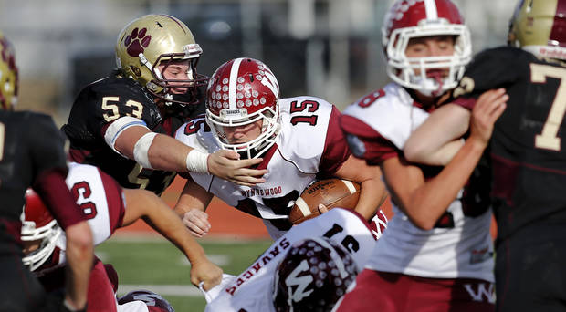 photo - Cashion's Tyler Jech, left, reaches to grab Wyneewod Jace Brown on this run up the middle of the Cashion defense. Cashion vs. Wynnewood at Norman in a Class A semifinal football game, Saturday, Dec. 1, 2012.     Photo by Jim Beckel, The Oklahoman