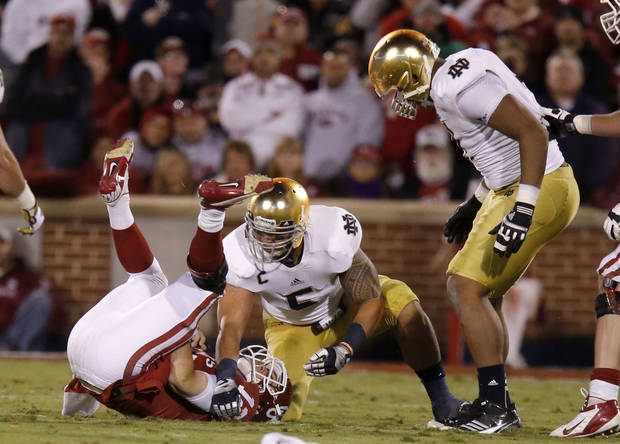 Notre Dame's Manti Te'o (5), center, and Stephon Tuitt (7) stand over OU's Landry Jones (12) after a sack during the college football game between the University of Oklahoma Sooners (OU) and the Notre Dame Fighting Irish at Gaylord Family-Oklahoma Memorial Stadium in Norman, Okla., Saturday, Oct. 27, 2012. Photo by Bryan Terry, The Oklahoman
