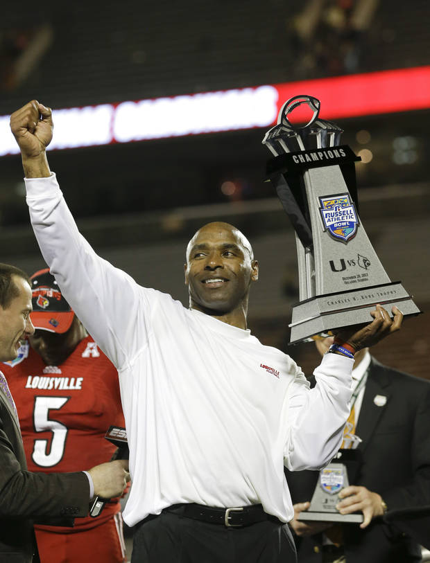photo - Louisville coach Charlie Strong holds the trophy after Louisville defeated Miami 36-9 in the Russell Athletic Bowl NCAA college football game in Orlando, Fla., Saturday, Dec. 28, 2013.(AP Photo/John Raoux)