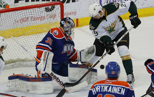photo - Yann Danis of the Oklahoma City Barons deflects the puck away as Alex Chiasson of the Texas Stars tries to score during an AHL hockey game at the Cox Convention Center in Oklahoma City, Friday, Dec. 21, 2012. Photo by Bryan Terry, The Oklahoman