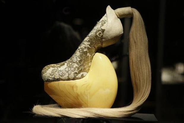 photo - This Feb. 11, 2013 photo shows a shoe, designed by Masaya Kushino, and made with lacquered Japanese cypress wood, human hair, and lace, displayed at the