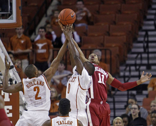 photo - Oklahoma guard Isaiah Cousins (11) comes down with a rebound against Texas guard Kendal Yancy (0) and Demarcus Holland (2) during the first half of an NCAA college basketball game Saturday, Jan. 4, 2014, in Austin, Texas. (AP Photo/Michael Thomas)