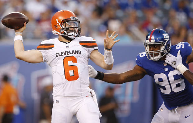Cleveland Browns quarterback Baker Mayfield (6) throws a pass away from New York Giants' Kareem Martin (96) during the first half of a preseason NFL football game Thursday, Aug. 9, 2018, in East Rutherford, N.J. (AP Photo/Adam Hunger)