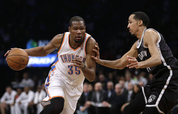 photo - Oklahoma City Thunder's Kevin Durant, left, moves around Brooklyn Nets' Shaun Livingston during the first half of an NBA basketball game Friday, Jan. 31, 2014, in New York. (AP Photo/Seth Wenig)
