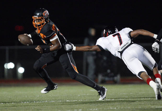 photo - Booker T. Washington quarterback Dominique Alexander (11) dodges a sack attempt by East Central's Kimmee Carson (7) at S.E. Williams Stadium, on Friday, Sept. 16, 2011. CORY YOUNG/Tulsa World