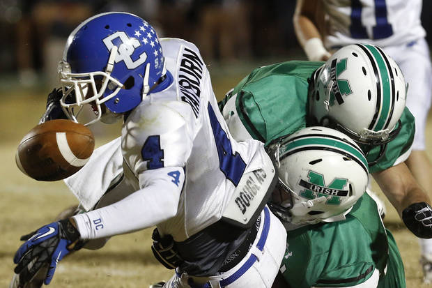 photo - Deer Creek wide receiver Jared Rayburn fumbles the ball as he is tackled by a pair of Irish defenders in the second quarter. McGuinness player Austin Hopfer (cq) recovered the ball. Deer Creek Antlers vs. Bishop McGuinness Fighting Irish at Pribil Stadium Friday night, Nov. 2, 2012.    Photo by Jim Beckel, The Oklahoman