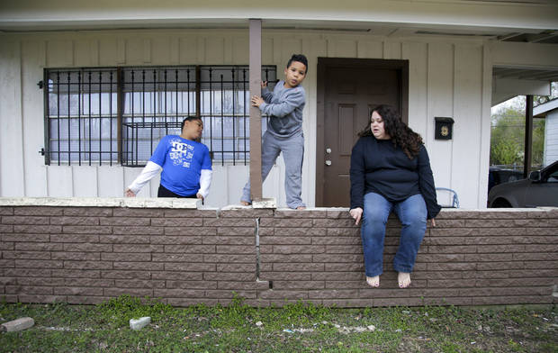 Desha Bailey tries to pose her sons for a portrait in front of their home in Tulsa. Bailey regained custody of her two sons after battling and recovering from a drug addiction. The boys were placed in foster care in Sapulpa after Bailey was arrested and placed in drug treatment. [Photo by Jessie Wardarski, Tulsa World]