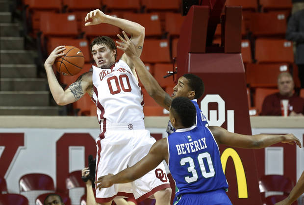 photo - Oklahoma's Ryan Spangler (00) grabs a rebound in front of Texas A&M Corpus Christi forward Jeff Beverly (30) and forward Zane Knowles, rear, during the first half of an NCAA college basketball game in Norman, Okla., Thursday, Dec. 5, 2013. (AP Photo/Sue Ogrocki)