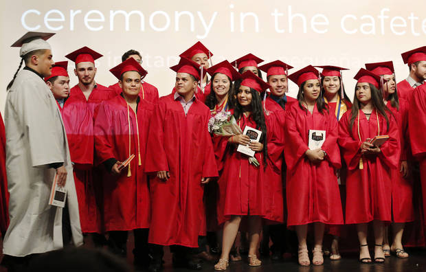 Graduates, in caps and robes, gather on stage for a group photo at the end of a special graduation ceremony to recognize 30 (ELL) English Language Learners at U.S. Grant High School. The ceremony was Monday afternoon, May 21, 2018. Photo by Jim Beckel, The Oklahoman