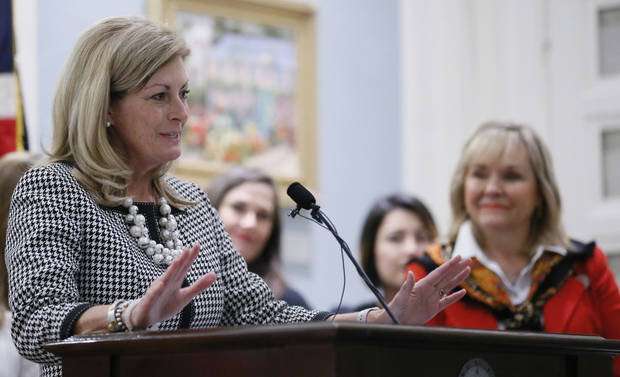 Oklahoma Gov. Mary Fallin, right, looks on as state Sen. Kim David, R-Porter, speaks during a news conference in Oklahoma City, Tuesday, April 11, 2017. Fallin announced that the state of Oklahoma and Tulsa-based Family & Children's Services (F&CS) have entered into a Pay for Success (PFS) contract aimed at reducing Oklahoma's nation-leading female incarceration rate by securing public-private investment in the successful Women in Recovery (WIR) prison diversion program. (AP Photo/Sue Ogrocki)