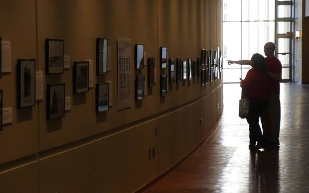 "Visitors look at the Oklahoma History Center's exhibit ""Wanted: Dead or Alive,"" a photography exhibit comprised of images of some of Oklahoma's most infamous criminals and lesser-known outlaws. It will be on display until Feb. 29. [Photo by Doug Hoke/The Oklahoman]"