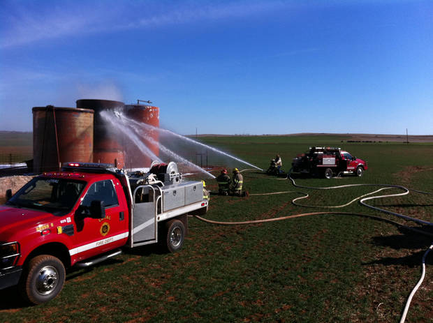 photo - Firefighters extinguish a fire at an oil well site  Sunday. Officials say someone intentionally shot at an oil holding tank in rural Kingfisher County, causing pressure to build up and the tank to explode.  Photo provided by Kingfisher Fire Chief Randy Poindexter