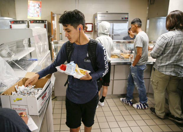 Caleb Wallace, 17, goes through the lunch line in the cafeteria at U.S. Grant High School in Oklahoma City, Wednesday, June 6, 2018. Oklahoma City Public Schools is providing summer meals at no cost to students at parks, splash pads and schools around the metro area between June 4 and July 20. Photo by Nate Billings, The Oklahoman