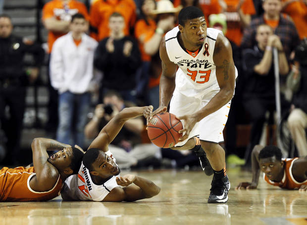 photo - Oklahoma State's Marcus Smart (33) picks up a loose ball in front of Texas' Julien Lewis (14), left, Oklahoma State's Markel Brown (22), middle, and Texas' Myck Kabongo (12) during a men's college basketball game between Oklahoma State University (OSU) and the University of Texas at Gallagher-Iba Arena in Stillwater, Okla., Saturday, March 2, 2013. OSU won, 78-65. Photo by Nate Billings, The Oklahoman