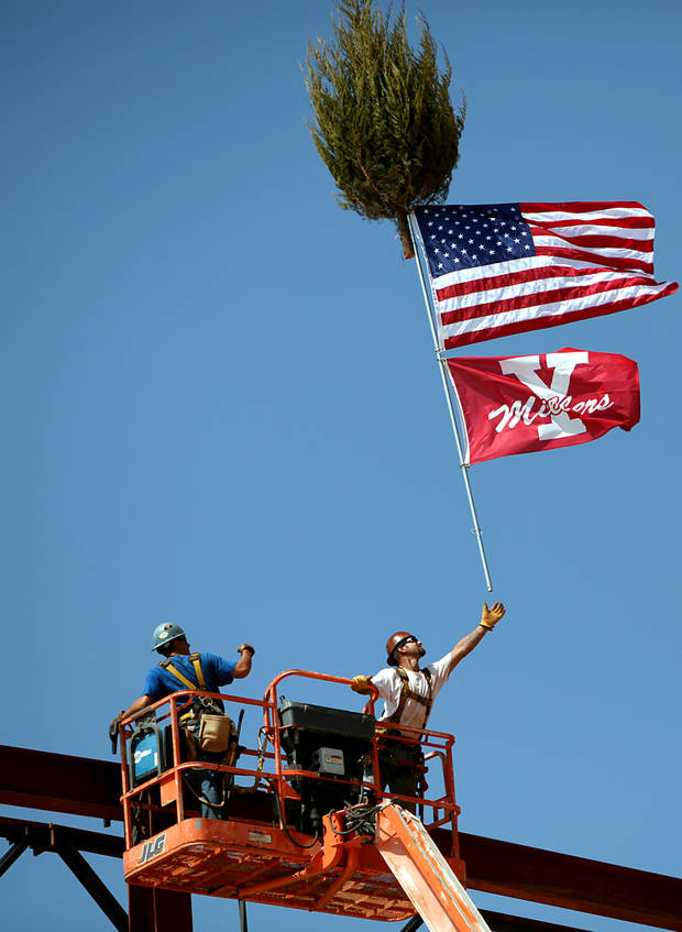 Aug. 31, 2010: Aaron East, left, and Dave Kaschmitter, ironworkers with All Steel, put up flags and a tree during a topping out ceremony at the new Yukon High School. [Photo by John Clanton, The Oklahoman Archives]