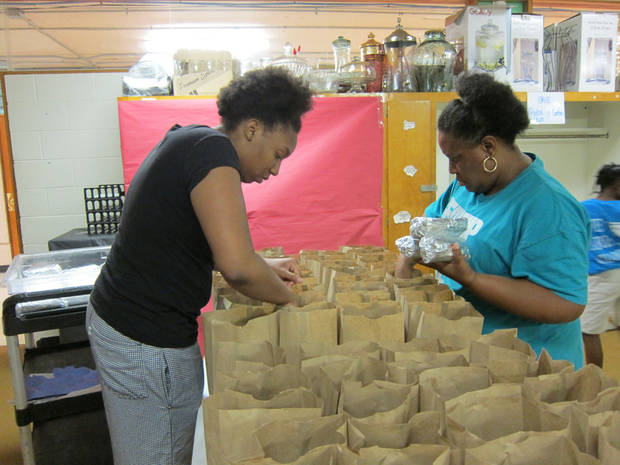 photo - Kambre Glover and Cherise Pendleton pack lunches into sacks to be distributed at summer meals sites through the Urban Initiatives program sponsored by the Oklahoma Southeast Jurisdition of the Church of God in Christ in partnership with the U.S. Department of Agriculture.  Photo by Carla Hinton, The Oklahoman