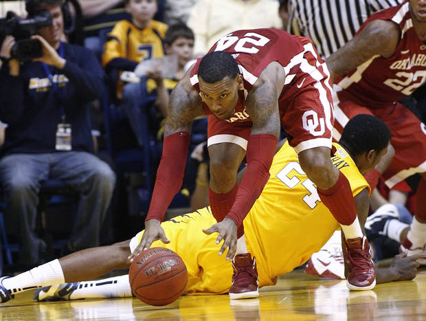 photo - Oklahoma's Romero Osby gets by West Virginia's Aaric Murray, lying on floor, for a loose ball on Saturday, Jan. 5, 2013, during the second half of an NCAA college basketball game in Morgantown, W.Va. Osby led Oklahoma with 21 points in a 67-57 win. (AP Photo/Randy Snyder) ORG XMIT: WVRS109