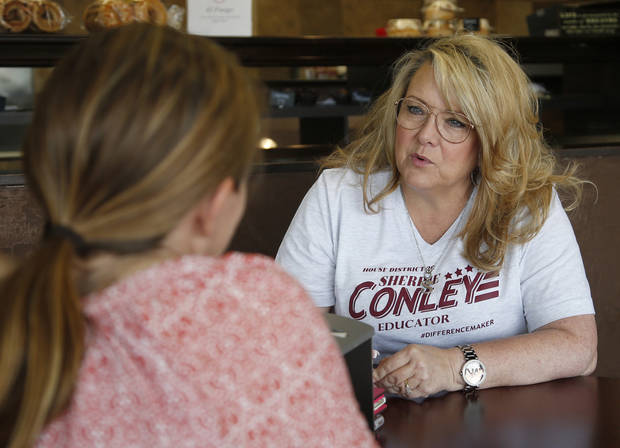 Elementary school principal Sherrie Conley, talks with a voter at a bagel shop in Norman, Okla. Conley ousted a three-term incumbent in Tuesday's Republican primary runoff election. (AP Photo/Sue Ogrocki, File)