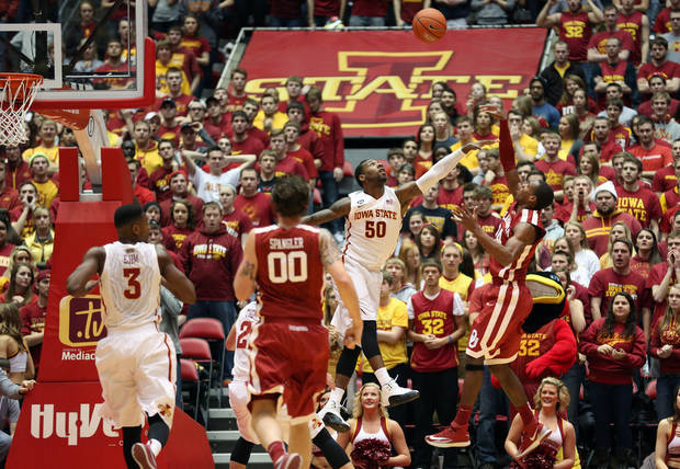 photo - Oklahoma guard Buddy Hield, right, puts up a shot over Iowa State guard DeAndre Kane (50) during the first half of an NCAA college basketball game in Ames, Iowa, Saturday, Feb. 1, 2014. (AP Photo/Justin Hayworth)