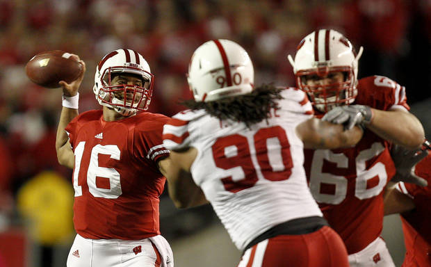photo - Wisconsin quarterback Russell Wilson (16) passes as Wisconsin offensive linesman Peter Konz (66) blocks Nebraska defensive tackle Terrence Moore (90) during the first half of an NCAA college football game Saturday, Oct. 1, 2011, in Madison, Wis. (AP Photo/Andy Manis) ORG XMIT: WIAM113