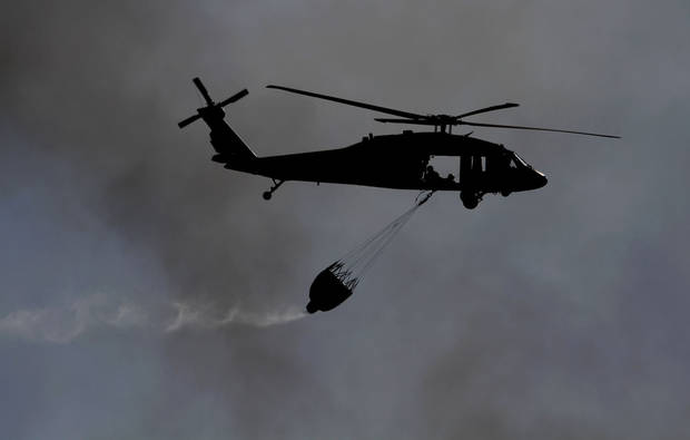 Oklahoma National Guard helicopter drops water on a large grassfire near Spencer Jones Road and Westminster, Wednesday, April 6, 2011 in Oklahoma City, Okla. Photo by Sarah Phipps, The Oklahoman ORG XMIT: KOD