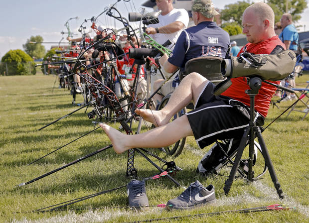 photo - Matt Stutzman, known as the Armless Archer uses his feet to set his arrow as he prepares to take part in the archery event during the Endeavor Games at the University of Central Oklahoma on Friday, June 7, 2013 in Edmond, Okla.  Photo by Chris Landsberger, The Oklahoman