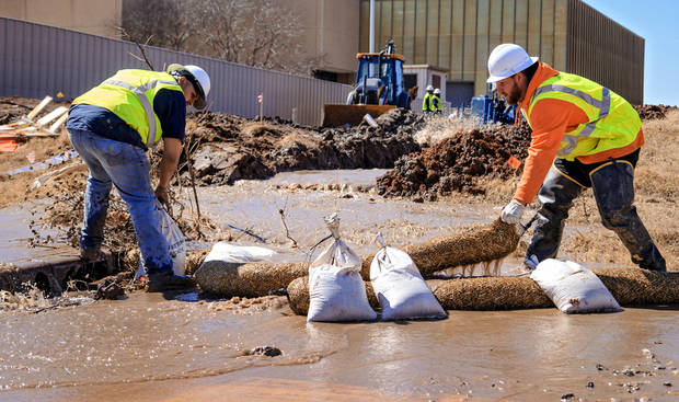 City Utilities Department workers redirected the flow of water from a broken 20-inch water main near SW 3 and E.K. Gaylord Boulevard in downtown Oklahoma City on Tuesday. [Photo by Chris Landsberger, The Oklahoman]