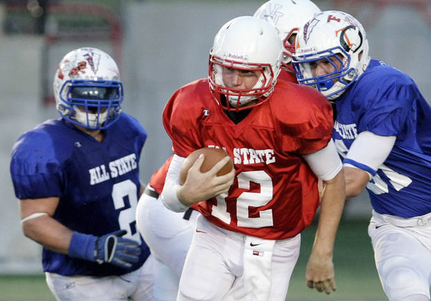 photo - West quarterback Garrett Lorah, center, finds a hole between the East's Hunter Hart and Tyler Clifton during their All State football game at Union High School in Tulsa, Okla., Friday, July 27, 2012. (AP Photo/Tulsa World Michael Wyke) ORG XMIT: OKTUL105