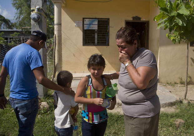 photo - In this Saturday, July 19, 2014 photo, Elsa Lopez, 57, cries as she receives her grandchildren, Sandra, 8, and Cesar, 5, who were deported along with their mother, from the United States a day earlier, in Tocoa, Honduras. Overwhelmed by unaccompanied minors and women with children crossing illegally, U.S. authorities have stepped up deportations back to Central America. (AP Photo/Esteban Felix)