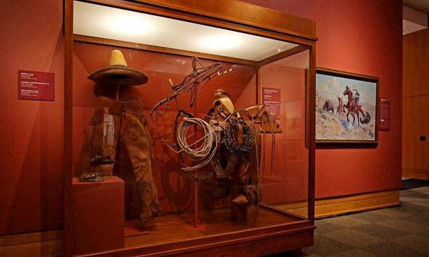"The National Cowboy & Western Heritage Museum's newly remodeled Atherton Gallery is seen on September 12, 2020. and A full vaquero rig complete with saddle, rope and hat accompanies a newly acquired painting, William Herbert Dunton's ""Fernando Roped One of the Bears and His Brother Caught Another."" [Doug Hoke/The Oklahoman]"