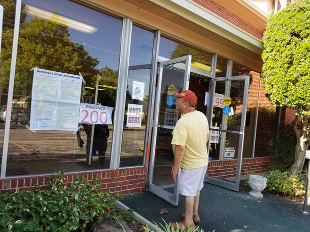 A voter reads a sign before walking into a north Oklahoma City precinct on Aug. 28, 2018. [Photo by Ben Felder