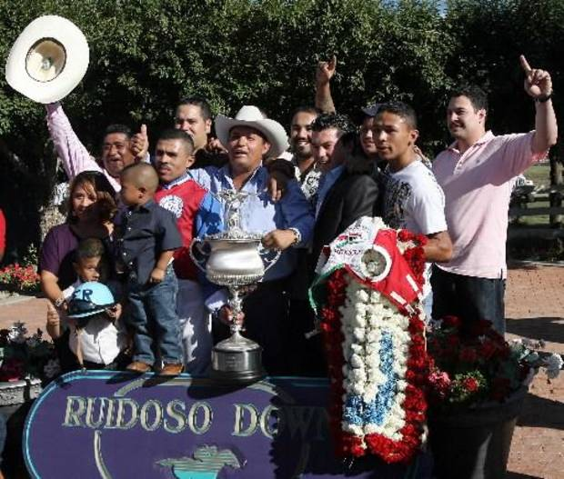 photo - In this photo taken Sept. 6, 2010, owner Jose Trevino Morales, center, acknowledges the crowd as he his joined by well-wishers and the trophy after Mr. Piloto won the All-American Futurity horse race at Ruidoso Downs, N.M. (AP Photo/The El Paso Times, Rudy Gutierrez)