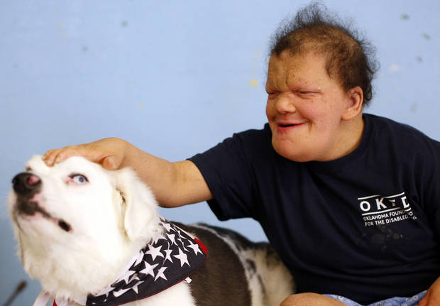 photo -  Amanda Holland pets Whiskey as the therapy dog visits the Oklahoma Foundation for the Disabled in Oklahoma City. Photo by Sarah Phipps, The Oklahoman   SARAH PHIPPS -