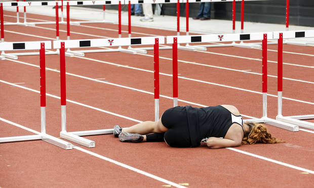 photo - Putnam City's Schuyler Wood lies on the track after clipping a hurdle and falling in the Class 6A 100-meter hurdles in 2013.  Photos by Chris Landsberger, The Oklahoman