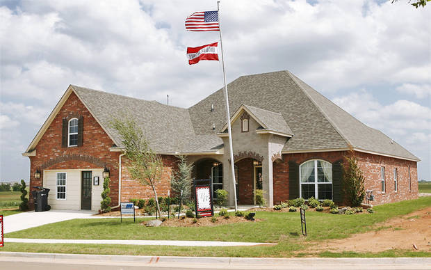 photo - Flags fly over the Brass Brick Design/Build model home at 3260 Orchard Ave. in The Grove addition at NW 192 and May Avenue.PHOTO BY JIM BECKEL, THE OKLAHOMAN