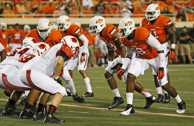 photo - OSU defenders stand on third down during a college football game between the Oklahoma State University Cowboys (OSU) and the Lamar University Cardinals at Boone Pickens Stadium in Stillwater, Okla., Saturday, Sept. 14, 2013. Photo by Nate Billings, The Oklahoman