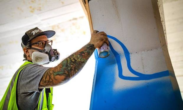 Artist Kris Kanaly works with spray paint to complete his mural 'Abstract Passages' on the Santa Fe Railroad over Main Street into Bricktown in Oklahoma City, Okla. on Friday, Oct. 20, 2017. [Chris Landsberger/The Oklahoman Archives]