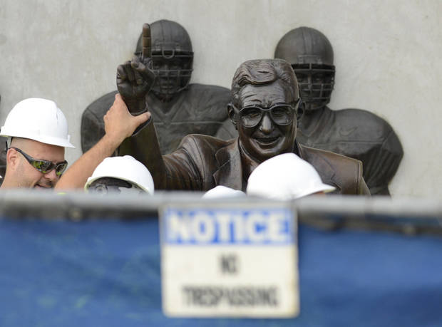 photo - Workers handle the statue of former Penn State football coach Joe Paterno before removing the statue Sunday, July 22, 2012, in State College, Pa. The famed statue of Paterno was taken down from outside the Penn State football stadium Sunday, eliminating a key piece of the iconography surrounding the once-sainted football coach accused of burying child sex abuse allegations against a retired assistant. (AP Photo/John Beale) ORG XMIT: PAJL102