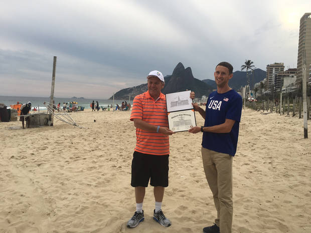Oklahoma State professor of business Bruce Barringer presents American pole vaulter Cale Simmons his diploma on Ipanema Beach in Rio de Janeiro. [PHOTO PROVIDED]